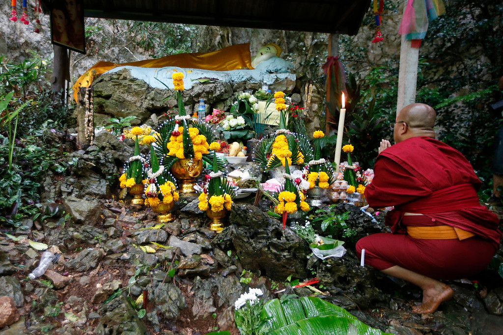 . A Thai Buddhist monk pray for 12 boys and their soccer coach, in Mae Sai, Chiang Rai province, northern Thailand Wednesday, June 27, 2018. Rain continued to fall and water levels kept rising Wednesday inside a cave in northern Thailand, frustrating the search for the boys and the coach who have been missing in the sprawling underground caverns since Saturday. (AP Photo/Sakchai Lalit)