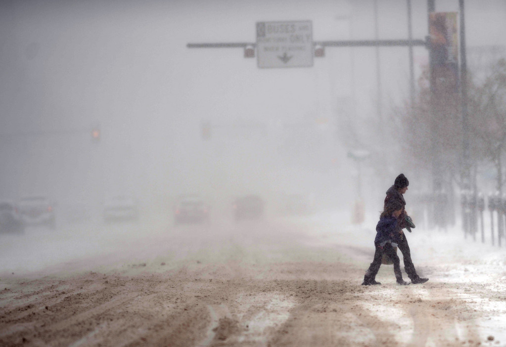 . DENVER, CO. - MARCH 23: People cross snow-covered Broadway near 5th Ave. Heavy snow continues to fall in the Denver area. Denver, Colorado. March 23, 2013. (Photo By Hyoung Chang/The Denver Post)