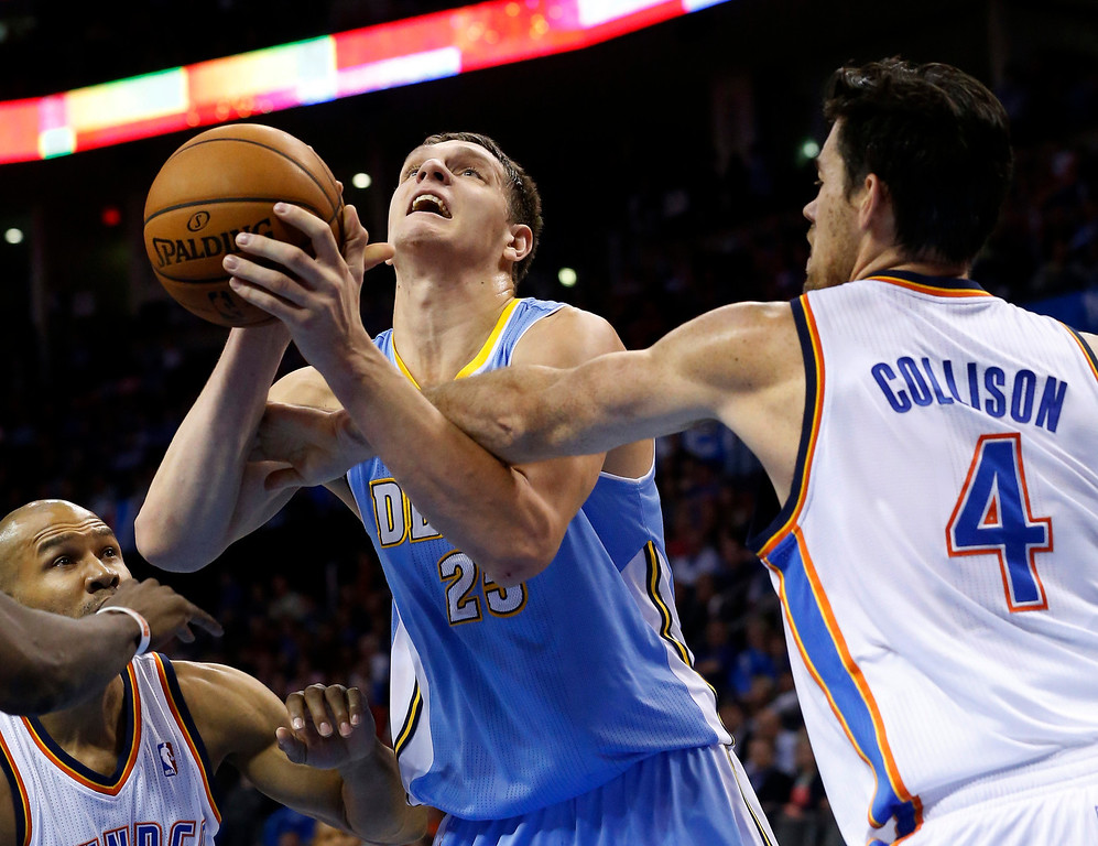 . Denver Nuggets center Timofey Mozqov (25) is fouled by Oklahoma City Thunder power forward Nick Collison (4) in the second quarter of an NBA basketball game in Oklahoma City, Monday, Nov. 18, 2013. (AP Photo/Sue Ogrocki)