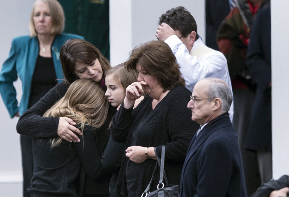 Description of . Mourners arrive for the funeral Mass of Jessica Rekos at St. Rose of Lima Roman Catholic Church December 18, 2012 in Newtown, Connecticut. Rekos, age 6, is one of the victims from last Friday's shooting at Sandy Hook Elementary School which took the lives of 20 students and 6 adults.  AFP PHOTO/Brendan SMIALOWSKI/AFP/Getty Images