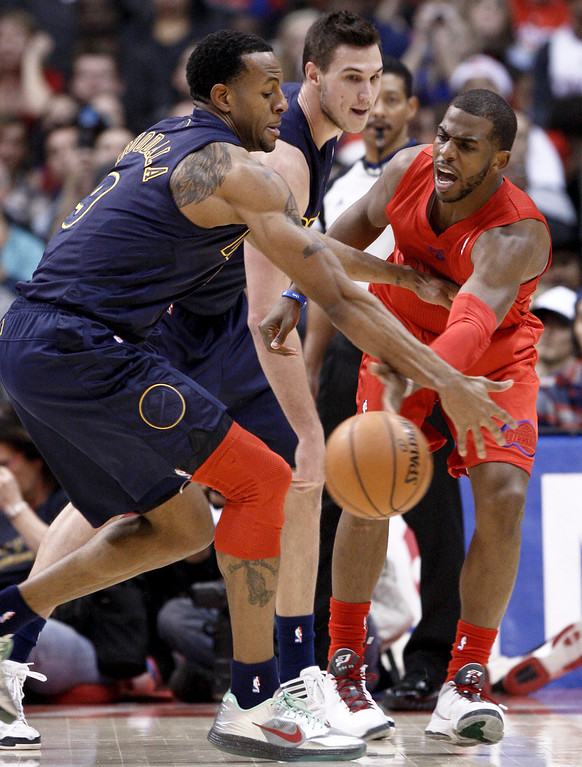 . Los Angeles Clippers guard Chris Paul, right, passes the ball under pressure from Denver Nuggets\' Andre Iguodala (9) and Danilo Gallinari, center, during the first half of their NBA basketball game, Tuesday, Dec. 25, 2012, in Los Angeles. (AP Photo/Jason Redmond)