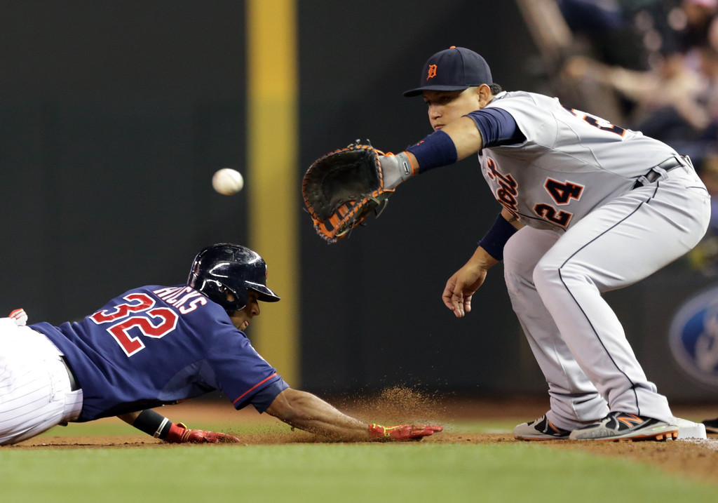 . Minnesota Twins\' Aaron Hicks, left, dives safely back to first as Detroit Tigers first baseman Miguel Cabrera reaches for the ball in a pickoff attempt in the fifth inning of a baseball game, Tuesday, Sept. 16, 2014, in Minneapolis. (AP Photo/Jim Mone)