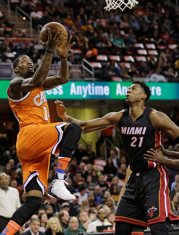 . Cleveland Cavaliers\' DeAndre Liggins, left, drives to the basket against Miami Heat\'s Hassan Whiteside in the first half of an NBA basketball game Friday, Dec. 9, 2016, in Cleveland. (AP Photo/Tony Dejak)