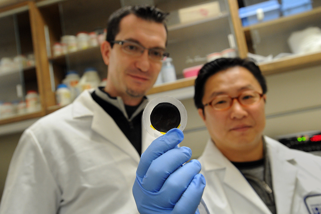 . Chemical engineers Francesco Fornasiero, left, and Sangil Kim, right, hold a piece of carbon nanotube fabric created at Lawrence Livermore National Laboratory in Livermore, Calif. on Friday, Dec. 7, 2012.  (Dan Honda/Staff)