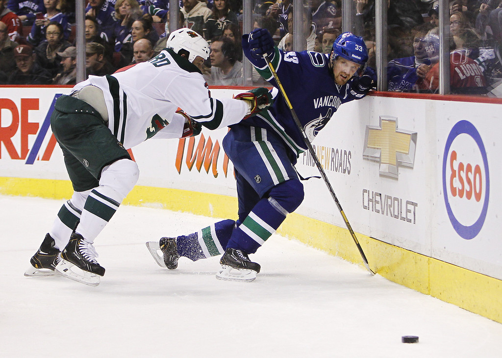 . Henrik Sedin #33 of the Vancouver Canucks is checked by Keith Ballard #2 of the Minnesota Wild during the second period of their NHL game at Rogers Arena on February 28, 2014 in Vancouver, British Columbia, Canada. (Photo by Ben Nelms/Getty Images)