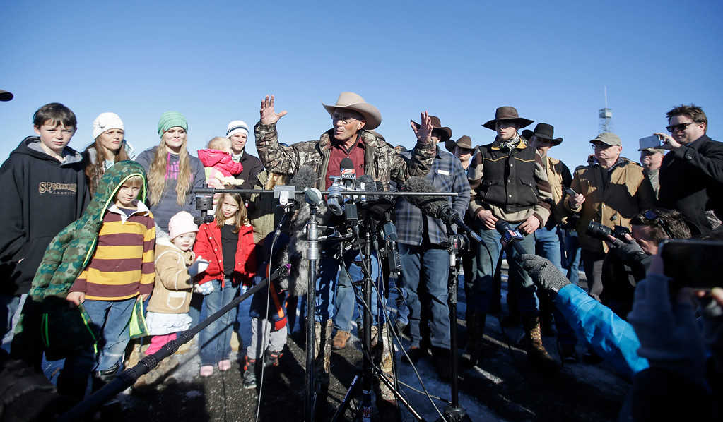 . LaVoy Finicum, center, a rancher from Arizona, speaks to reporters as his family looks on, left, during a news conference at Malheur National Wildlife Refuge Friday, Jan. 8, 2016, near Burns, Ore. Ammon Bundy, the leader of a small, armed group occupying a national wildlife refuge in Oregon says the activists have no immediate plans to leave. Bundy spoke to reporters Friday, a day after meeting with a local sheriff who asked the group to go. (AP Photo/Rick Bowmer)