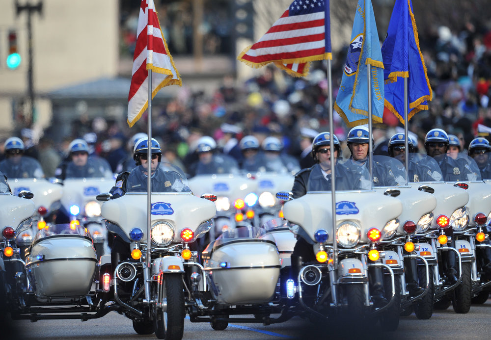 Description of . Police on motorcyles lead as US President Barack Obama and First Lady Michelle Obama walk along Pennsylvania Avenue during the parade following Obama's second inauguration as the 44th US president on January 21, 2013 in Washington, DC.  MLADEN ANTONOV/AFP/Getty Images