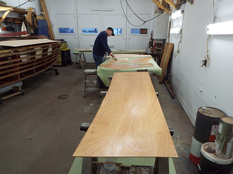 Appling the first of three coats of epoxy to the inside of the plywood skin.