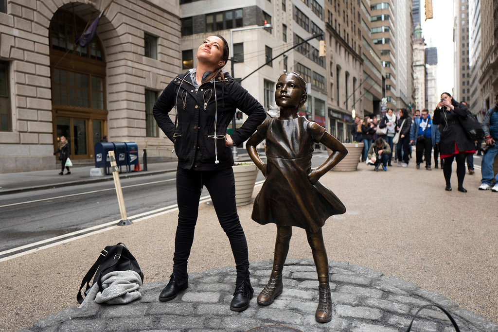 ". A woman strikes a pose in front of a statue titled ""Fearless Girl\"" on Wednesday, March 8, 2017, in New York. A big investment firm, State Street Global Advisors, put the statue there to highlight International Women\'s Day. The work by artist Kristen Visbal. (AP Photo/Mark Lennihan)"