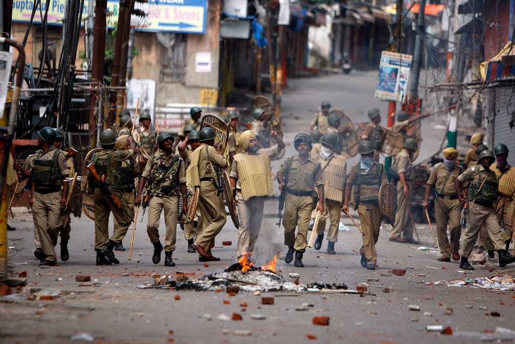 . Indian paramilitary soldiers patrol during a protest against the state government after rival communities clashed in Kishtwar, in Jammu, India, Saturday, Aug. 10,2013. Indian forces fired warning shots Saturday to enforce a curfew and to push angry people back into their homes in Kishtwar, in the Indian portion of Kashmir where clashes between Muslims and Hindus during Eid celebrations killed at least two people and injured another 24.(AP Photo/Channi Anand)