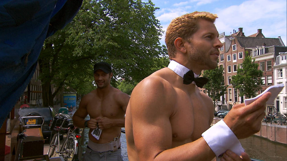 ". ""Fishy Kiss (Amsterdam, Netherlands)\""--In Detour B, Chippendale Friends James (left) and Jaymes (right) must earn thirty Euros while playing a Dutch street organ in order to receive the next clue on THE AMAZING RACE on the CBS Television Network. Photo: CBS ©2012 CBS Broadcasting, Inc. All Rights Reserved"