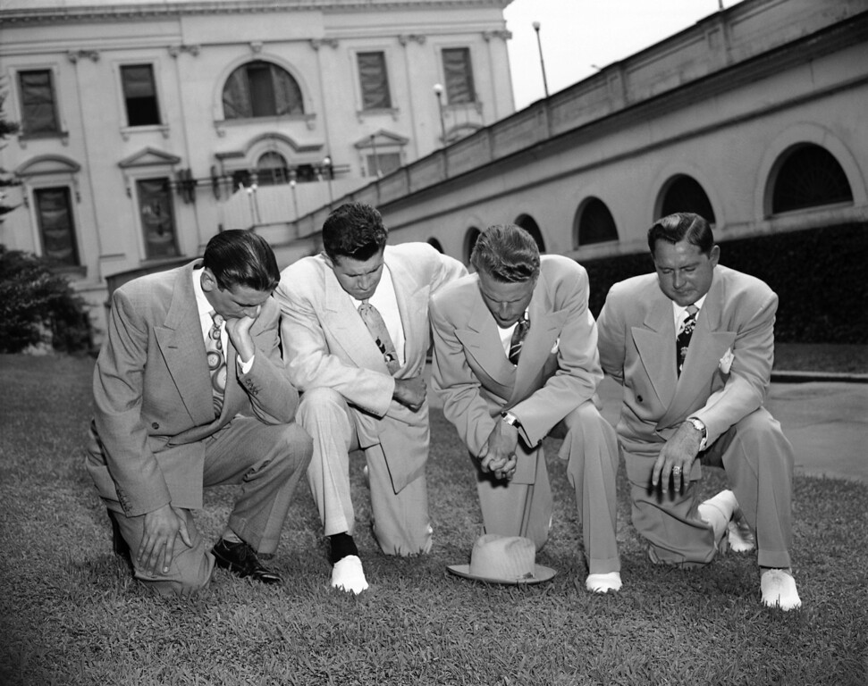 . Evangelist Billy Graham (second from right), kneels in prayer on the White House lawn in Washington July 14, 1950 with three friends, asking Devine aid for President Truman in his handling of the Korean crisis. He had just finished a half-hour visit with the Chief Executive. With him from left to right are Jerry Beavan, Clifford Barrows and Grady Wilson. (AP Photo)