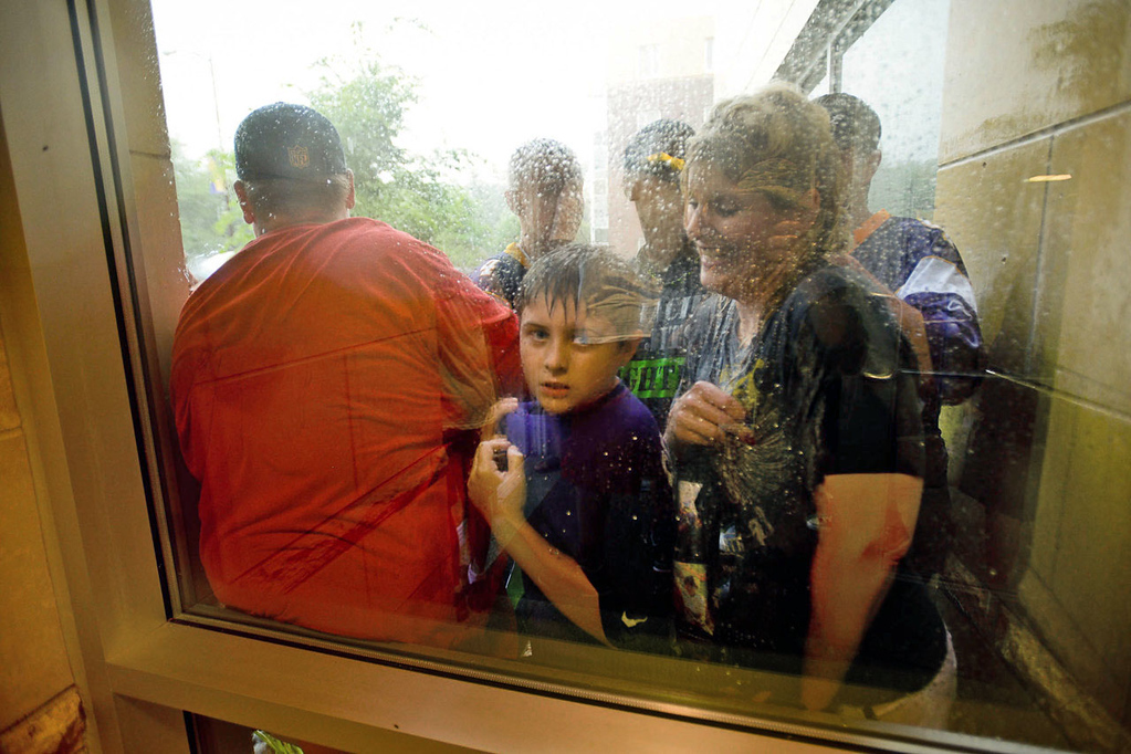 . Vikings fans snug up against a window as they wait out a heavy rainstorm while awaiting the players\' arrivals at training camp.  (Pioneer Press: Ben Garvin)