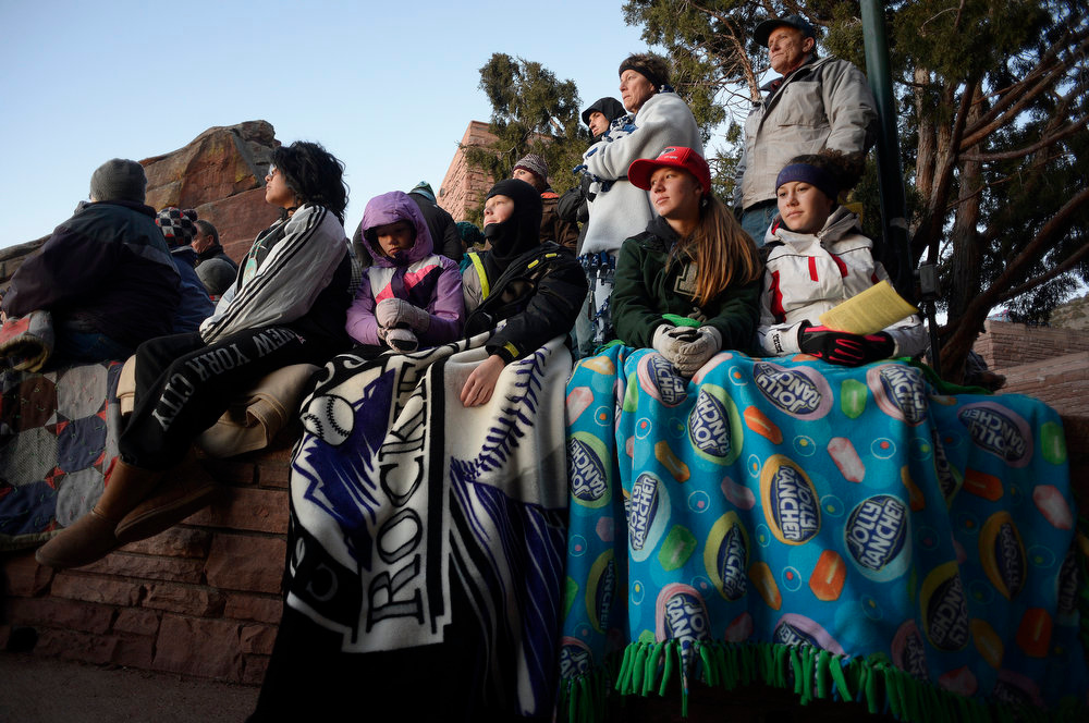 . From left to right Erin McCarty, 9 and her brother Kyle, 11 and Emily Gibbons, 18 and her sister Alyssa, of Denver, stay cuddled up under blankets to stay warm during the service.  Thousands of people turned out for the sixty sixth annual Easter sunrise service at Red Rocks Amphitheatre in Golden on March 31st, 2013.The sun rose at 6:45 am under cloudless skies and this year\'s service was pleasant with warmer temperatures than in previous years.  The service, sponsored by the Colorado Council of Churches, was led by Reverend Dr. Jim Ryan and presided over by Reverend Dr. Janet Forbes. (Photo By Helen H. Richardson/ The Denver Post)