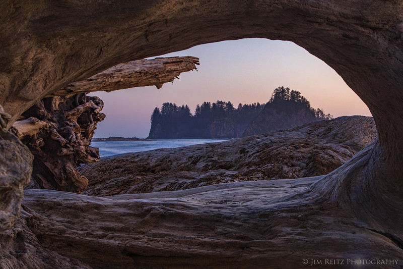 James Island near La Push, Washington - viewed at sunset thru an opening in driftwood logs.