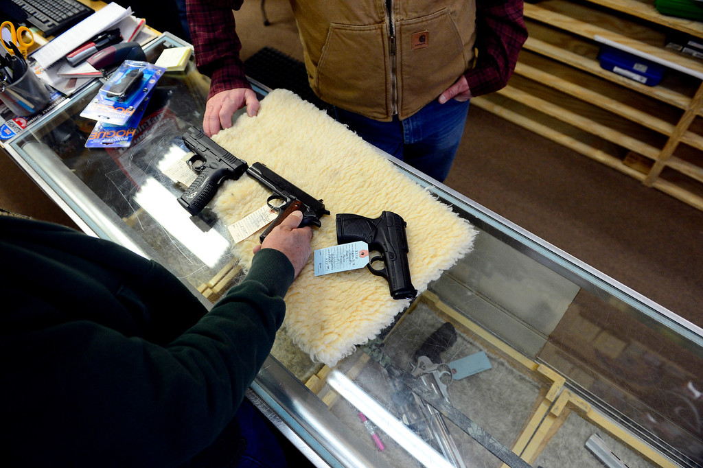 . MONTE VISTA, CO - FEBRUARY 26: Andrew Gallegos buys a handgun from Valley Guns owner Carlton Thomas. Gun owners in southern Colorado largely agree that responsible ownership begins at home. (Photo by AAron Ontiveroz/The Denver Post)