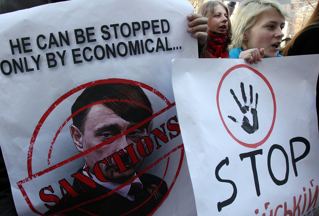 . A pro-Ukrainian activist holds a poster (L) with Russian President Vladimir Putin caricatured as Adolf Hitler during a rally in front of the German Embassy in Kiev on March 11, 2014. Pro-Moscow lawmakers in Crimea voted for independence from Ukraine on March 11 in a precursor to a referendum this weekend for the region to become part of Russia. ANOVANATOLII STEPANOV/AFP/Getty Images