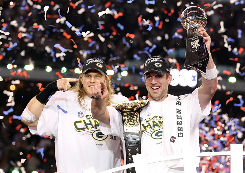 . Super Bowl MVP Aaron Rodgers #12 of the Green Bay Packers holds up the Vince Lombardi Trophy as Clay Matthews #52 looks on after winning Super Bowl XLV 31-25 against the Pittsburgh Steelers at Cowboys Stadium on February 6, 2011 in Arlington, Texas.  (Photo by Al Bello/Getty Images)