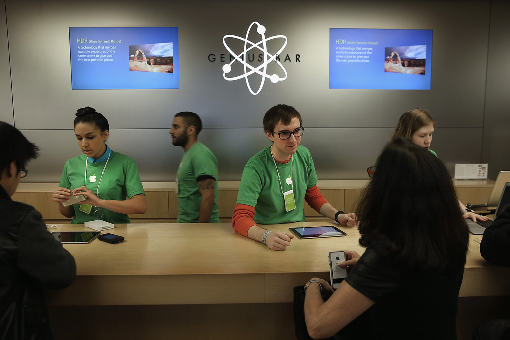 . Apple Genius bar employees assist customers at the company\'s Fifth Avenue store on Earth Day in Midtown Manhattan on April 22, 2014 in New York City. (Photo by John Moore/Getty Images)