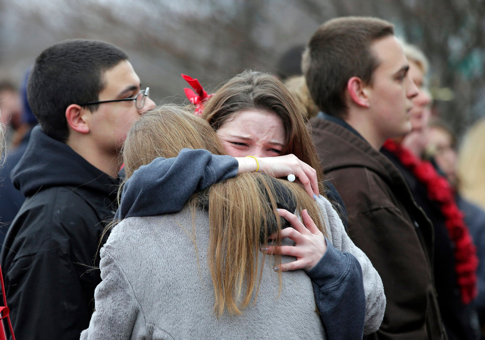 Description of . Two students hug at a memorial service in Chardon, Ohio Wednesday, Feb. 27, 2013 during a march to a memorial ceremony for three classmates who died in a school shooting rampage one year ago, Wednesday, Feb. 27, 2013. The march ended at the courthouse where 18-year-old shooter T.J. Lane pleaded guilty to all charges in February. (AP Photo/Mark Duncan)