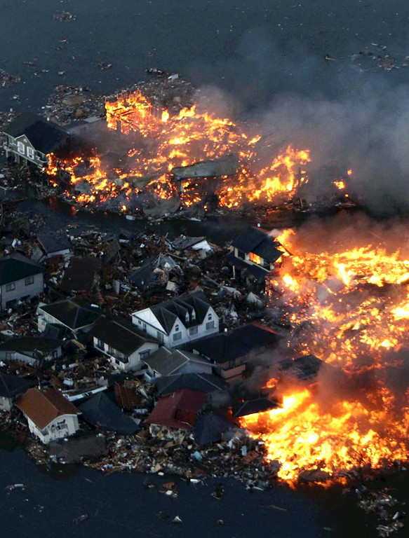 . This aerial shot shows houses in flame after being hit by a tsunami at Natori city in Miyagi prefecture, northern Japan on March 11, 2011. A massive 8.9-magnitude earthquake shook Japan, unleashing a powerful tsunami that sent ships crashing into the shore and carried cars through the streets of coastal towns. (STR/AFP/Getty Images)