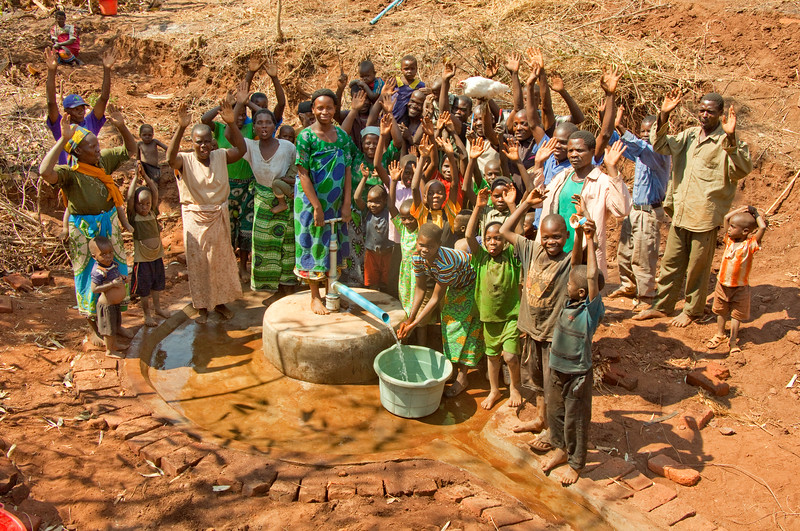 Excitement reaches a crescendo as the first water is pumped from the new well.