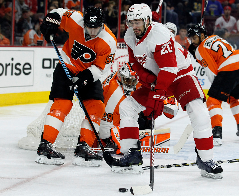 . Philadelphia Flyers\' Nick Schultz (55) left, and the Detroit Red Wings\' Drew Miller (20), front right, battle for control of the puck while goalie Ray Emery (29) watches during the first period of an NHL hockey game Saturday, Oct. 25, 2014, in Philadelphia. (AP Photo/Tom Mihalek)