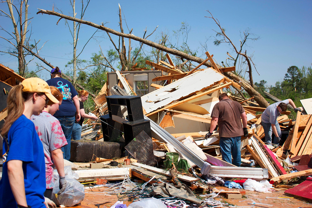 . The Barnes family with the help of friends salvage what is left of their home that was damaged from severe weather on Tuesday, April 29, 2014 in Tupelo, Miss.  (AP Photo/Hunt Mercier)