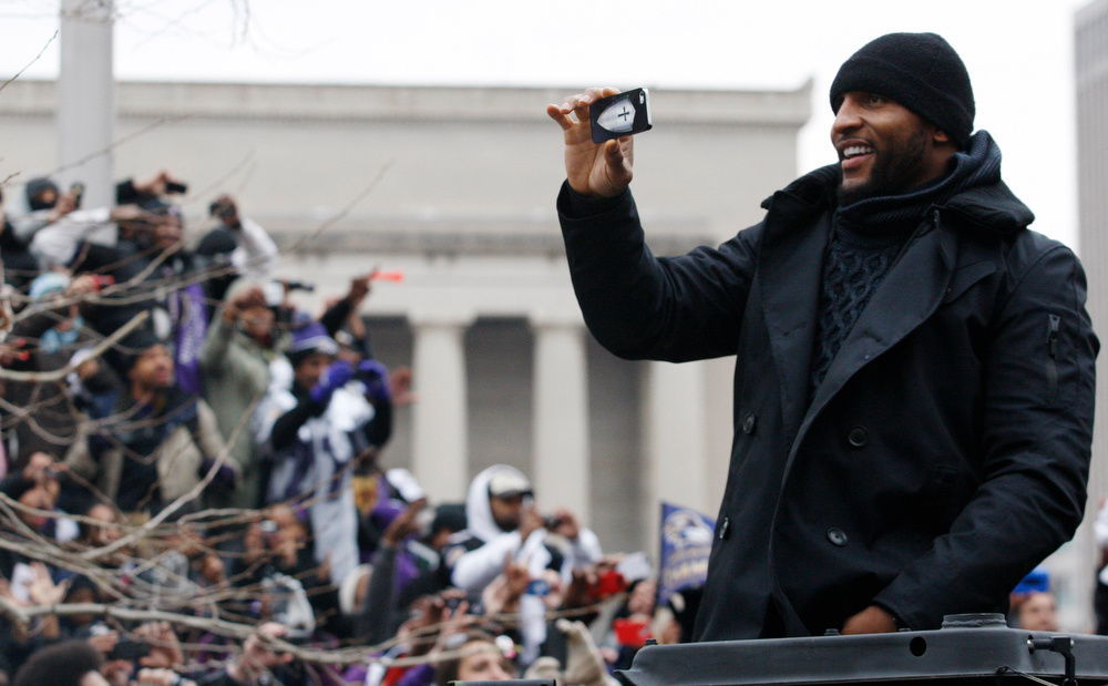 Description of . Baltimore Ravens retiring linebacker Ray Lewis takes pictures of fans on the team's parade route in Baltimore, Maryland February 5, 2013. The Ravens defeated the San Francisco 49ers to win the NFL championship.   REUTERS/Richard Clement