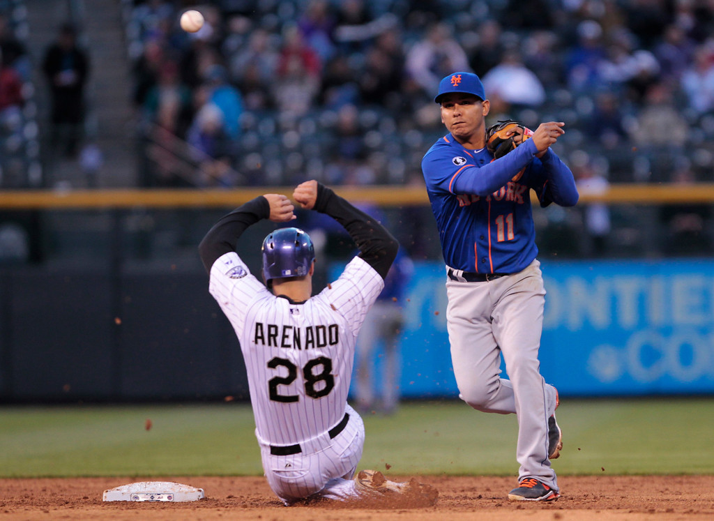 . New York Mets shortstop Ruben Tejada (11) throws to first base after forcing out Colorado Rockies\' Nolan Arenado (28) on a double play in the third inning of a baseball game in Denver, Thursday, May 1, 2014. Rockies\' Carlos Gonzalez was out at first base. (AP Photo/Joe Mahoney)