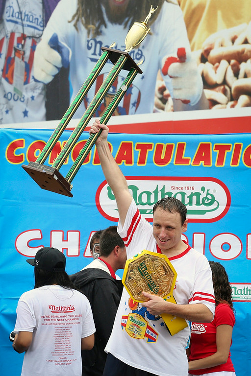 . Joey Chestnut raises his trophy in the air after winning Nathan\'s Famous Fourth of July International Hot Dog Eating contest at Coney Island, Friday, July 4, 2014, in New York. Chestnut finished first by consuming 61 hotdogs and buns. (AP Photo/John Minchillo)