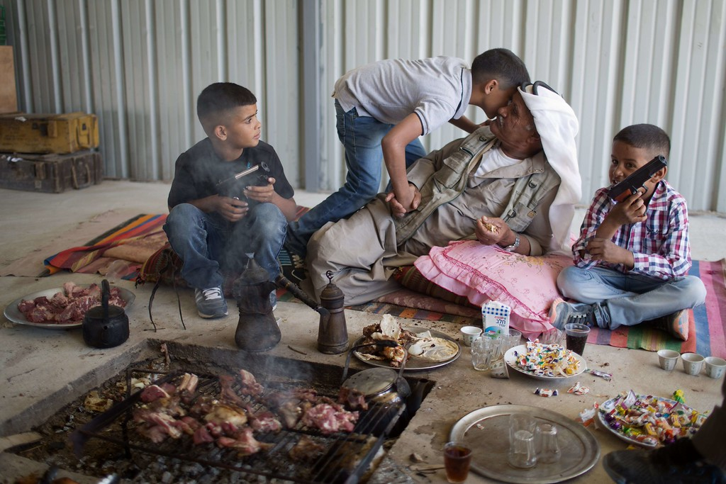 . Bedouins from the Zanun family which is part of the Azazme tribe, eat a holiday meal after slaughtering one of their sheep on the first day of the Eid al-Adha holiday on October 15, 2013 in their village of Wadi Naam, currently unrecognized by Israeli authorities, near the southern city of Beersheva in the Israeli Negev desert.  AFP PHOTO/MENAHEM KAHANA/AFP/Getty Images