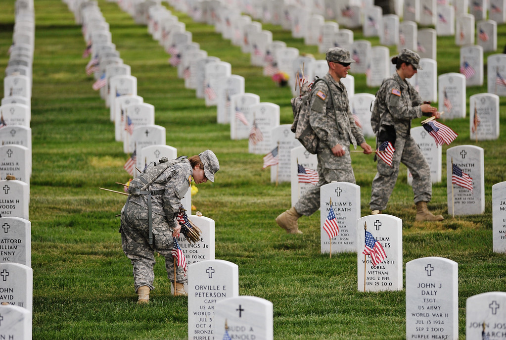 . Staff Sergeant Karrin Kampa (L) of the Third US Infantry Regiment, The Old Guard, place flags in front of graves at Arlington National Cemetery on May 23, 2013 in Arlington, Virginia ahead of Memorial Day.  AFP PHOTO/Mandel NGAN/AFP/Getty Images