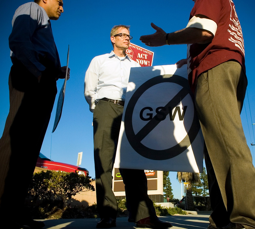 . John Dewey of Golden State Water Company, listens to Hal Hargrave, right, and Corey Calaycay, left, as the group Claremonters Against Outrageous Water Rates march in front of Golden State Water Company�s Claremont.  (Staff photo/Inland Valley Daily Bulletin)