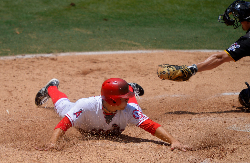 . Los Angeles Angels\' J.B. Shuck, left scores on a fielders choice by Mike Trout as Pittsburgh Pirates catcher Michael McKenry makes a late tag during the second inning of their baseball game, Sunday, June 23, 2013, in Anaheim, Calif.  (AP Photo/Mark J. Terrill)