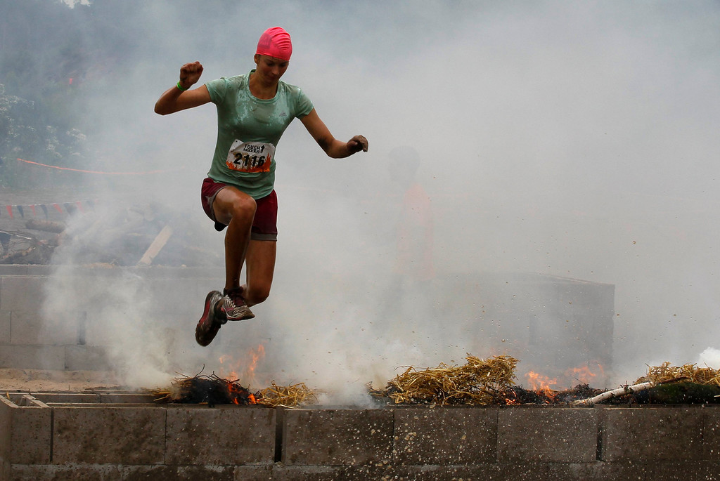". A female participant of the ""Tough Mudder\"" endurance event series jumps over an open fire of the \""Fire Walker\"" obstacle in the Fursten Forest, a former British Army training ground near the north-western German city of Osnabrueck July 13, 2013. The hardcore but un-timed event over 16 km (10 miles) was designed by British Special Forces to test mental as well as physical strength. Some 4,000 competitors had to overcome obstacles of common human fears, such as fire, water, electricity and heights.   REUTERS/Wolfgang Rattay"