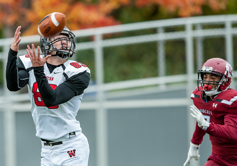 Wesleyan's Matthew Simco hauls in a perfect pass after getting seperation from Bates' Coy Candelario, right, before scampering into the endzone for a touchdown during Saturday's game. (Russ Dillingham/Sun Journal)