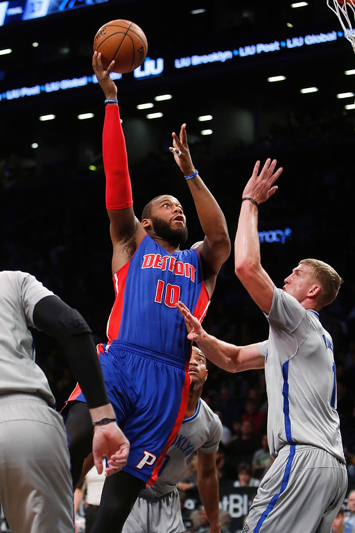 . Detroit Pistons\' Greg Monroe (10) shoots over Brooklyn Nets\' Mason Plumlee, right, during the first quarter of an NBA basketball game Sunday, Dec. 21, 2014, in New York. (AP Photo/Jason DeCrow)