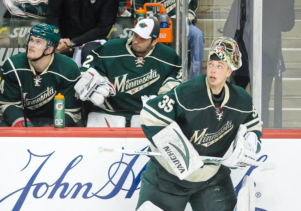 . Minnesota goalie Darcy Kuemper skates back to position while back-up goalie Niklas Backstrom, background, parks on the bench following an injury to starting goalie Josh Harding in the second period against the Blackhawks.  (Pioneer Press: Ben Garvin)