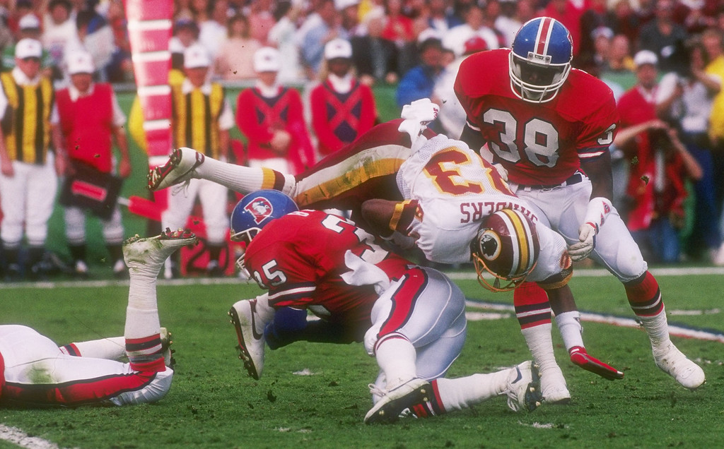 . Wide receiver Ricky Sanders #83 of the Washington Redskins is stopped by the Denver Broncos running back Ken Bell #35 and defensive back Bruce Plummer #38 during Super Bowl  XXII at Jack Murphy Stadium in San Diego, California. Rick Stewart/Allsport