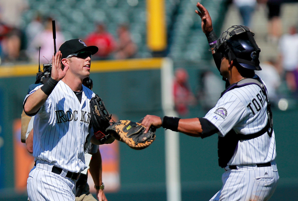 . Colorado Rockies\' Corey Dickerson, left, high-fives Yorvit Torrealba, right, who had an unassisted double play after a baseball game against the San Diego Padres on Wednesday, Aug. 14, 2013, in Denver. (AP Photo/Barry Gutierrez)
