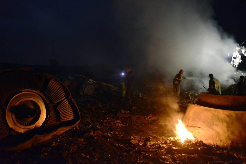 """. Firefighters extinguish a fire, on July 17, 2014, amongst the wreckages of the malaysian airliner carrying 295 people from Amsterdam to Kuala Lumpur after it crashed, near the town of Shaktarsk, in rebel-held east Ukraine. Ukrainian President Petro Poroshenko said on Thursday that the Malaysia Airlines jet that crashed over rebel-held eastern Ukraine may have been shot down.\""""We do not exclude that the plane was shot down and confirm that the Ukraine Armed Forces did not fire at any targets in the sky,\"""" Poroshenko said in a statement posted on the president\'s website. AFP PHOTO/ ALEXANDER  KHUDOTEPLY/AFP/Getty Images"""