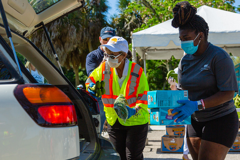 Sharon Madden, left and LyDona Lewis load food items in the back of a car at Dreher Park where the Tree of Life Resource Center hosted a drive thru community food distribution event in West Palm Beach, Tuesday, May 5, 2020.  The event was sponsored by Schumacher Automotive Group. It was estimated that about 500 cars passed through the site in Dreher Park and about 600 families received food which included produce, meats and diary and  non-perishables food items. [JOSEPH FORZANO/palmbeachpost.com]