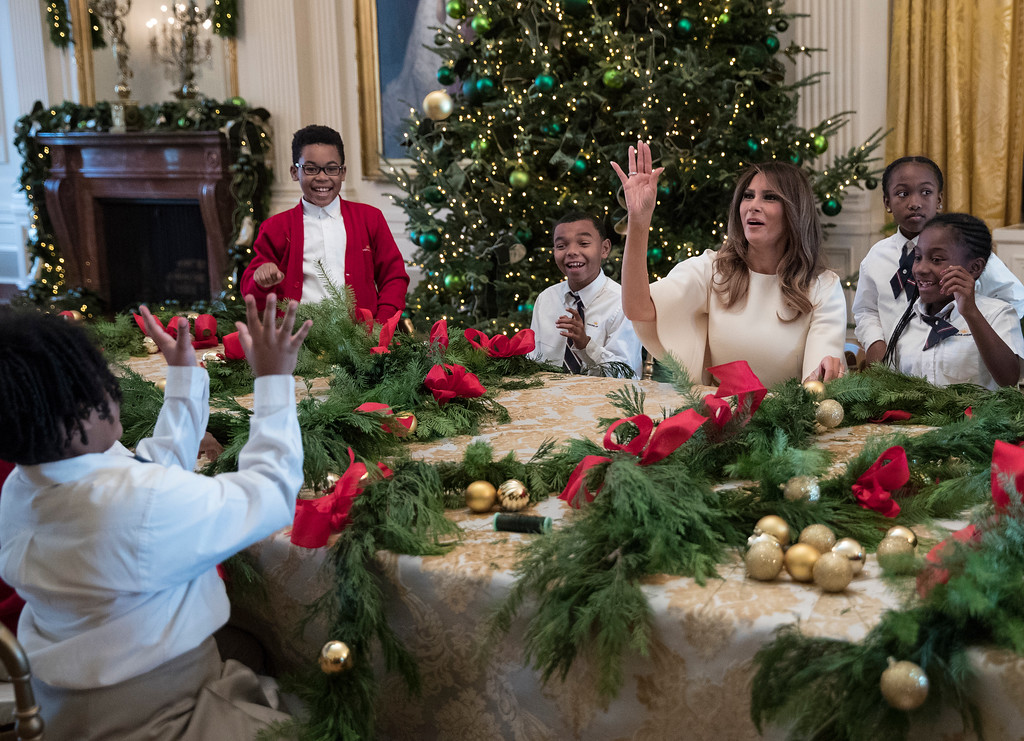 """. First lady Melania Trump tosses an ornament to a child across the table after one was tossed to her as she visits with children in the East Room among the 2017 holiday decorations with the theme \""""Time-Honored Traditions\"""" at the White House in Washington, Monday, Nov. 27, 2017. The First Lady honored 200 years of holiday traditions at the White House. (AP Photo/Carolyn Kaster)"""
