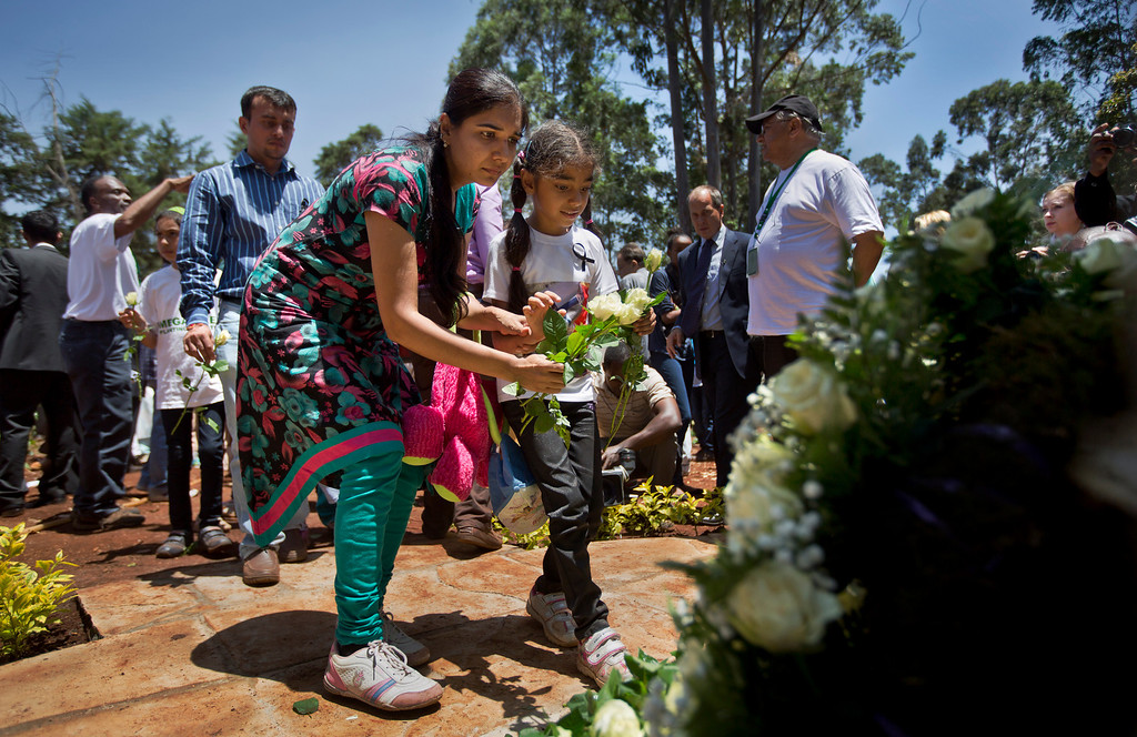 . Relatives of those who died lay white roses at a stone memorial, during a memorial service marking the one-month anniversary of the the Sept. 21 Westgate Mall terrorist attack, in Karura Forest in Nairobi, Kenya Monday, Oct. 21, 2013. (AP Photo/Ben Curtis)
