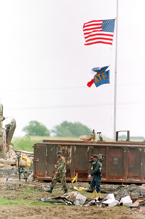 . The Texas flag and the ATF flag hang by one corner with the U.S. flag over the site where the Branch Davidian compound once stood in Waco, Tx, May 4, 1993.  Investigators are still searching the area for bodies from the April 19th fire.  The bodies of 72 people, including cult leader David Koresh, have been removed so far.  (AP Photo/Ron Heflin)