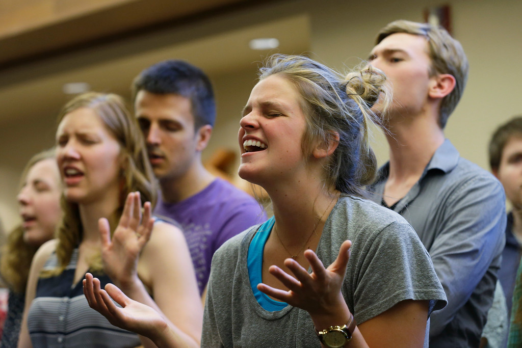 . A woman sings at a service at the First Free Methodist Church Thursday, June 5, 2014 at Seattle Pacific University in Seattle, where a shooting took place Thursday afternoon.(AP Photo/Ted S. Warren)