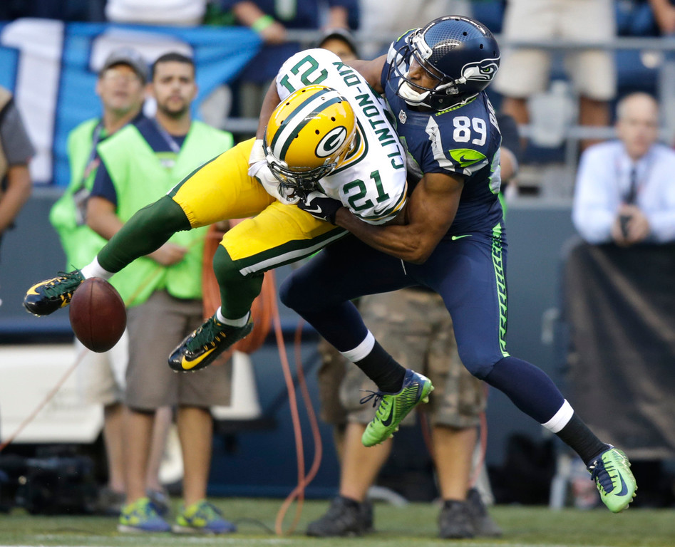 . Seattle Seahawks\' Doug Baldwin, right, breaks up an interception attempt by Green Bay Packers free safety Ha Ha Clinton-Dix (21) in the first half of an NFL football game, Thursday, Sept. 4, 2014, in Seattle. (AP Photo/Stephen Brashear)