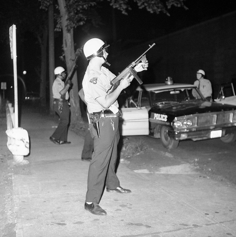 . A police officer aims a Tommy gun toward the roof of a theater in the riot-torn Hough area in Cleveland, Ohio, July 19, 1966. Police said a sniper had been firing from the roof tonight but managed to escape. (AP Photo/Julian C. Wilson)
