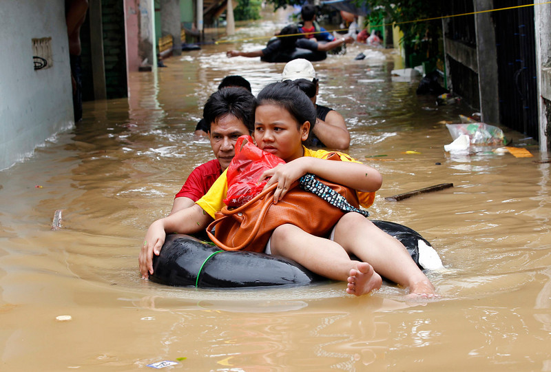 . A woman sits on a rubber float as she is evacuated from her flooded housing complex in Jakarta January 16, 2013. Floods inundated several areas of Jakarta due to the overflow of the Ciliwung River and several days of heavy rains in the capital city, local media reported on Wednesday.    REUTERS/Enny Nuraheni